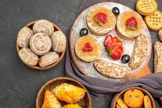 Vue de dessus de délicieuses crêpes avec des fruits et des gâteaux sucrés dans l'obscurité