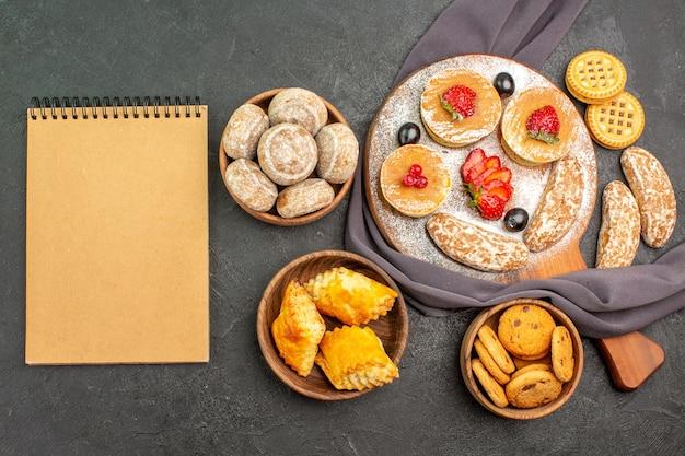 Vue de dessus de délicieuses crêpes avec des fruits et des gâteaux sucrés sur un sol sombre