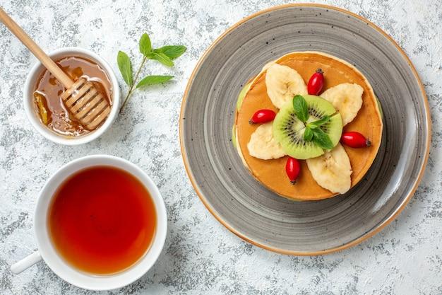 Vue de dessus de délicieuses crêpes avec des fruits tranchés et une tasse de thé sur une surface blanche, un dessert sucré, un gâteau de couleur pour le petit-déjeuner