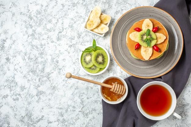 Vue de dessus de délicieuses crêpes avec des fruits tranchés et une tasse de thé sur une surface blanche, des fruits sucrés, des desserts sucrés, des gâteaux de couleur pour le petit-déjeuner