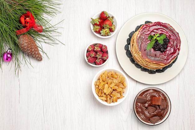 Vue de dessus de délicieuses crêpes à la gelée avec des raisins secs et du chocolat sur le blanc
