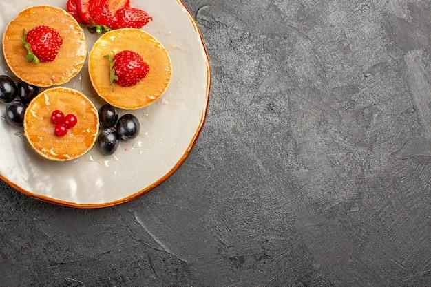 Vue de dessus de délicieuses crêpes peu formées avec des fruits dans le noir