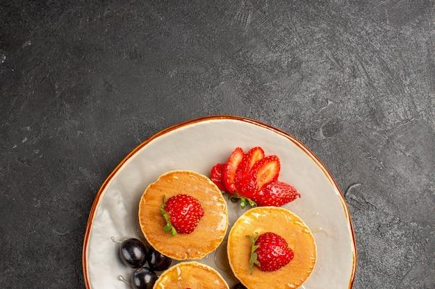 Vue de dessus de délicieuses crêpes peu formées avec des fruits sur une tarte aux fruits au sol sombre