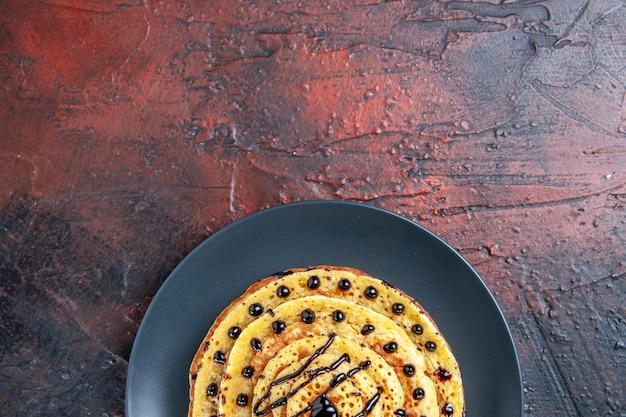 Vue de dessus de délicieuses crêpes sucrées avec du glaçage sur la surface sombre