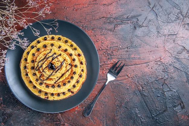 Vue de dessus de délicieuses crêpes sucrées avec du glaçage sur une surface sombre