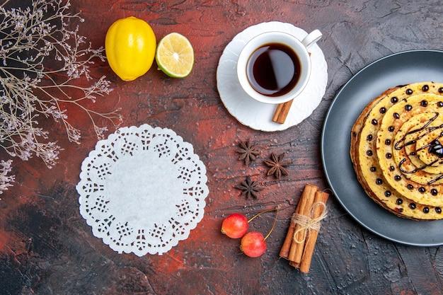 Vue de dessus de délicieuses crêpes sucrées avec du thé sur la surface sombre