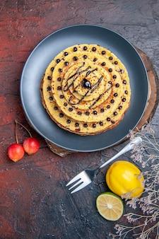 Vue de dessus de délicieuses crêpes sucrées avec glaçage au chocolat sur une surface sombre