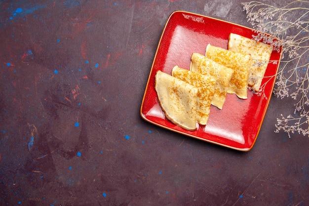 Vue de dessus de délicieuses crêpes sucrées à l'intérieur d'une assiette rouge dans l'obscurité