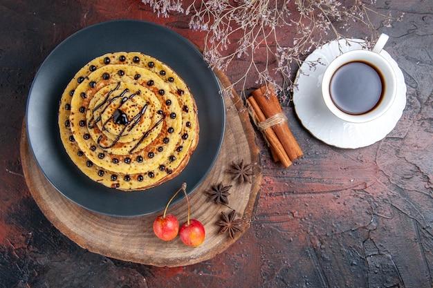 Vue de dessus de délicieuses crêpes sucrées avec une tasse de thé sur une surface sombre