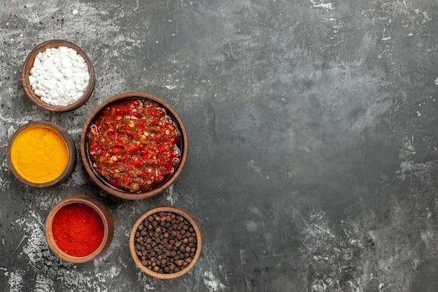 Vue de dessus de délicieuses épices adjika différentes dans de petits braillements sur fond gris