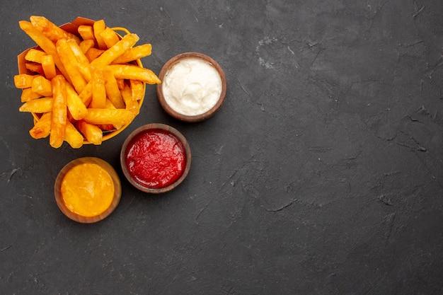 Vue de dessus de délicieuses frites avec des assaisonnements sur fond sombre burger fast-food plat de pommes de terre repas