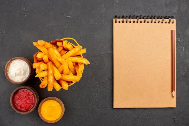 Vue de dessus de délicieuses frites avec des assaisonnements sur fond sombre plat de pommes de terre fast-food burger repas