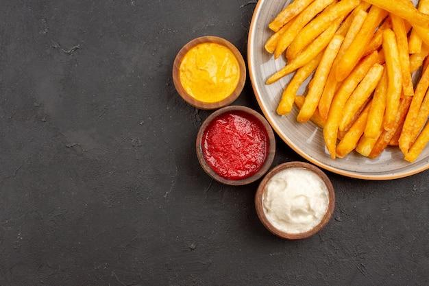 Vue de dessus de délicieuses frites avec des assaisonnements sur fond sombre plat de pommes de terre repas fast-food burger