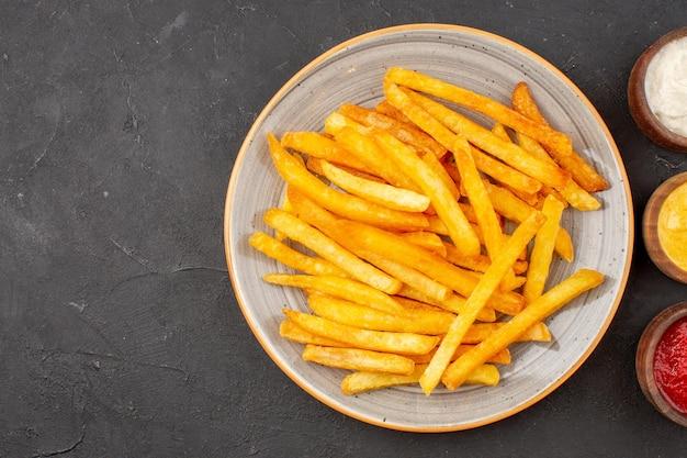 Vue de dessus de délicieuses frites avec des assaisonnements sur fond sombre plat de restauration rapide burger repas de pommes de terre