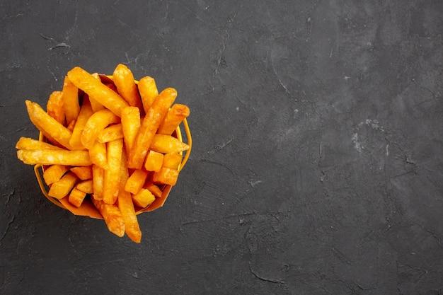 Vue de dessus de délicieuses frites à l'intérieur du paquet sur le repas de burger de plat de pommes de terre de restauration rapide sur fond sombre