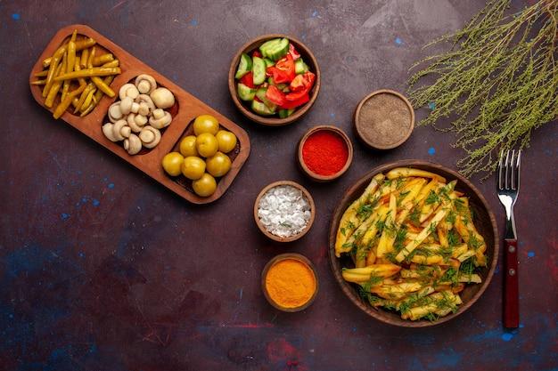 Vue de dessus de délicieuses frites avec des légumes verts et différents assaisonnements sur un bureau sombre