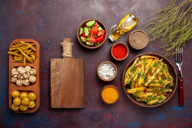 Vue de dessus de délicieuses frites avec des légumes verts et différents assaisonnements sur la surface sombre