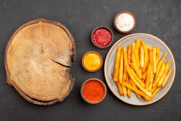 Vue de dessus de délicieuses frites avec des sauces sur fond sombre repas de restauration rapide burger plat de pommes de terre