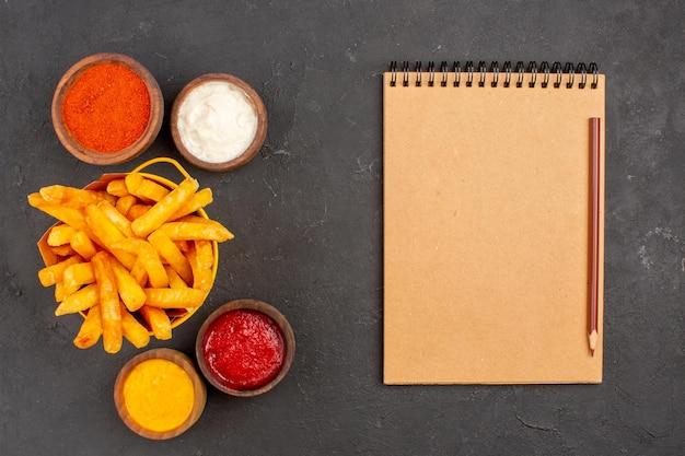 Vue de dessus de délicieuses frites avec des sauces sur le plat de fond sombre burger fast-food repas de pommes de terre