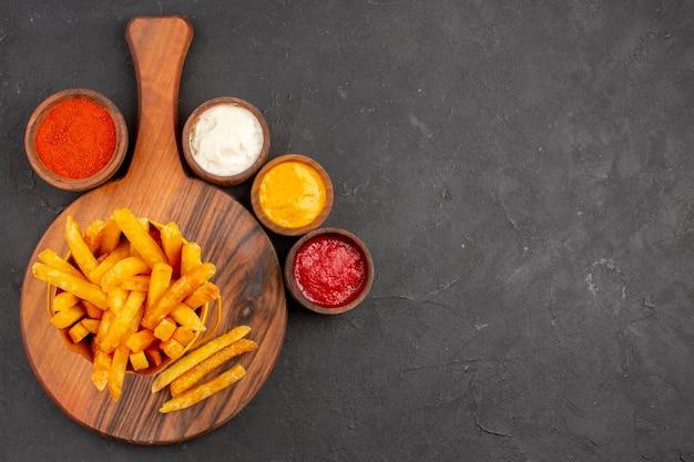 Vue de dessus de délicieuses frites avec sauces sur tableau noir