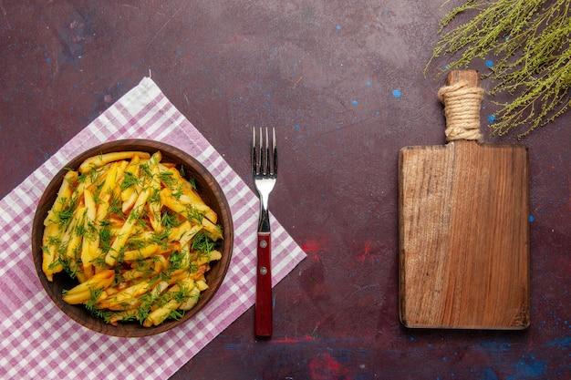 Vue de dessus de délicieuses frites avec des verts sur un bureau sombre
