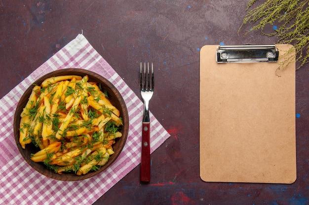 Vue de dessus de délicieuses frites avec des verts sur la surface sombre