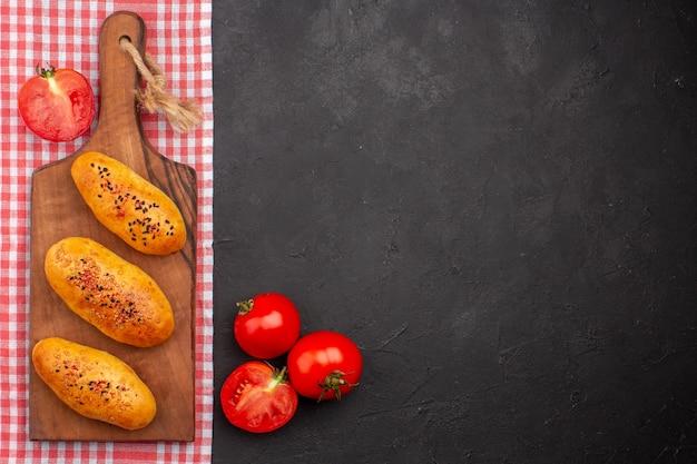 Vue de dessus de délicieuses galettes cuites au four avec différents assaisonnements sur fond gris foncé pâte cuire au four gâteau à la viande au four