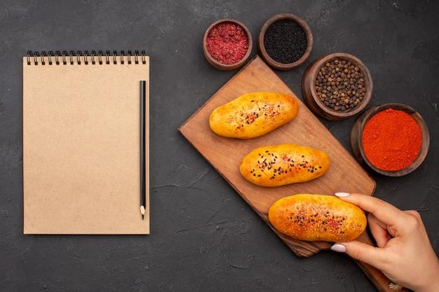 Vue de dessus de délicieuses galettes cuites au four avec différents assaisonnements sur le fond sombre pâte cuire au four pâtisserie gâteau à la viande