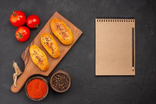 Vue de dessus de délicieuses galettes cuites au four fraîchement sorties du four avec des tomates sur le fond gris tarte four pâte pâtisserie viande gâteau cuire