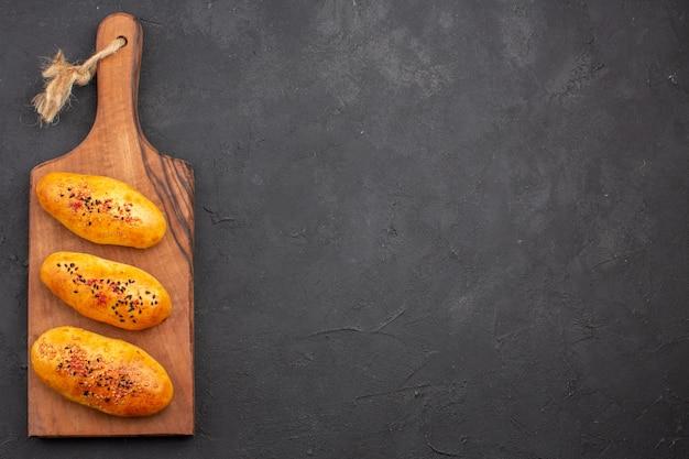 Vue de dessus de délicieuses galettes fraîchement sorties du four sur le fond sombre pâte à tarte pâtisserie four viande gâteau cuire