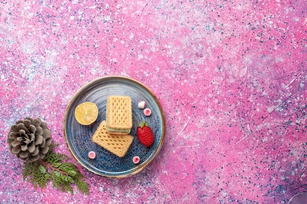 Vue de dessus de délicieuses gaufres avec surface rose fraise