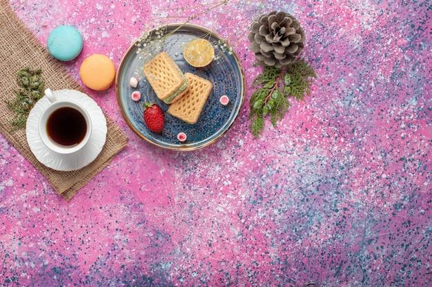 Vue de dessus de délicieuses gaufres avec tasse de thé et macarons sur surface rose
