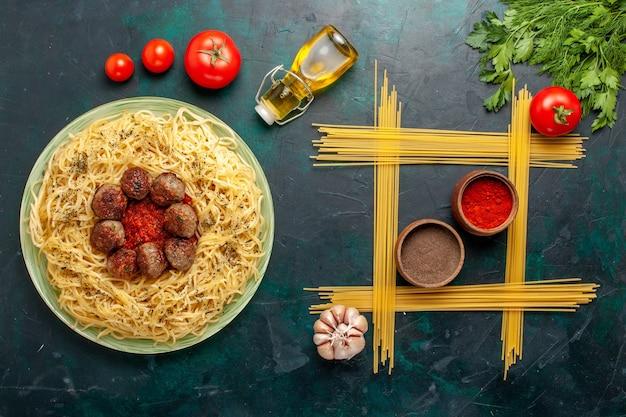 Vue de dessus de délicieuses pâtes italiennes aux boulettes de viande et sauce tomate sur le fond bleu foncé pâte pâtes plat repas dîner alimentaire italie