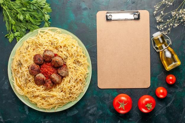 Vue de dessus de délicieuses pâtes italiennes aux boulettes de viande et sauce tomate sur fond bleu pâte plat de pâtes viande dîner alimentaire italie