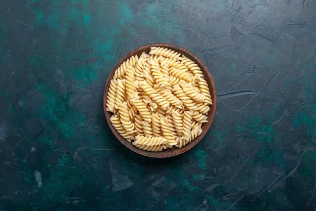 Vue de dessus de délicieuses pâtes italiennes à l'intérieur du pot brun sur bureau bleu foncé pâtes italiennes repas repas dîner cuisine cuisine pâte