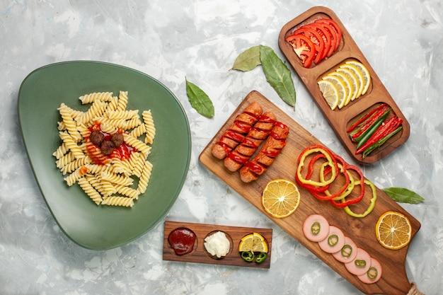 Vue de dessus de délicieuses pâtes italiennes avec des légumes et du citron sur un bureau léger repas repas plat de cuisine italienne dîner