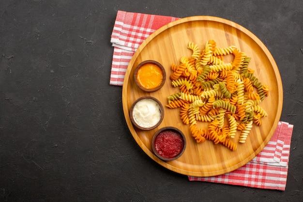 Vue de dessus de délicieuses pâtes italiennes pâtes en spirale cuites inhabituelles sur fond sombre plat repas cuisson pâtes dîner
