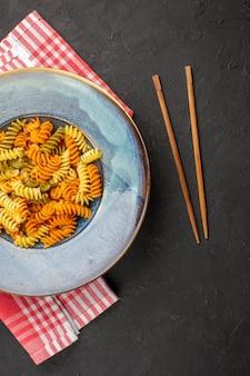 Vue de dessus de délicieuses pâtes italiennes pâtes en spirale cuites inhabituelles à l'intérieur de la plaque sur fond sombre plat de pâtes dîner repas cuisson