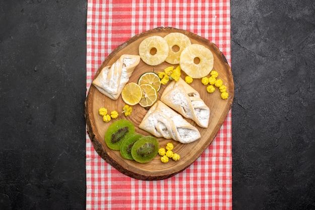 Vue de dessus de délicieuses pâtisseries avec des anneaux d'ananas séchés et des kiwis sur un espace gris foncé