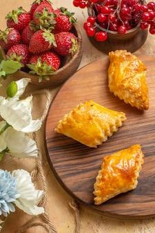 Vue de dessus délicieuses pâtisseries aux noix avec des fruits sur un bureau en bois
