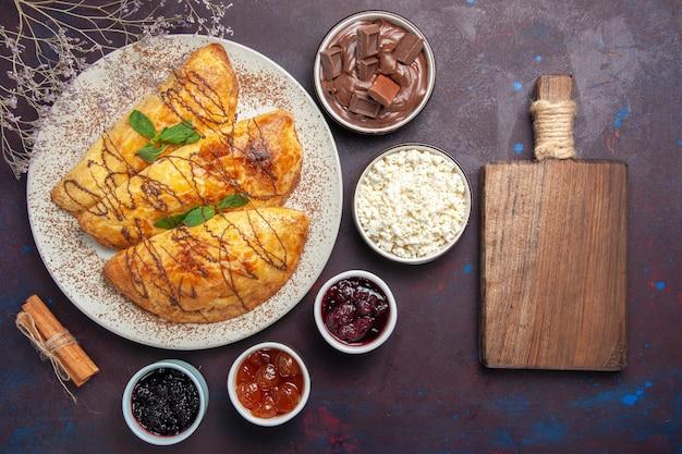 Vue de dessus de délicieuses pâtisseries avec de la confiture et du fromage cottage sur fond sombre pâtisserie gâteau sucré biscuit au sucre