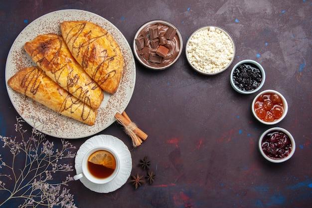 Vue de dessus de délicieuses pâtisseries cuites au four avec tasse de confiture de thé sur un espace sombre