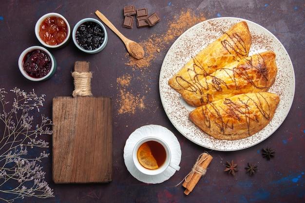 Vue de dessus de délicieuses pâtisseries cuites au four avec une tasse de thé et de confiture sur un bureau sombre