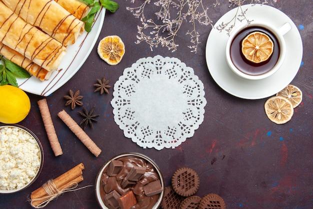 Vue de dessus de délicieuses pâtisseries sucrées au citron et au chocolat sur un espace sombre