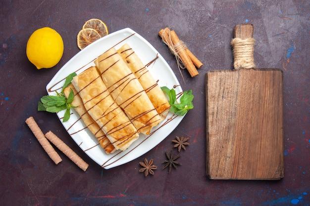 Vue de dessus de délicieuses pâtisseries sucrées au citron sur l'espace sombre
