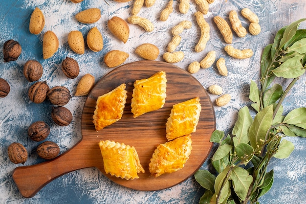Vue de dessus de délicieuses pâtisseries sucrées aux noix sur une surface bleue