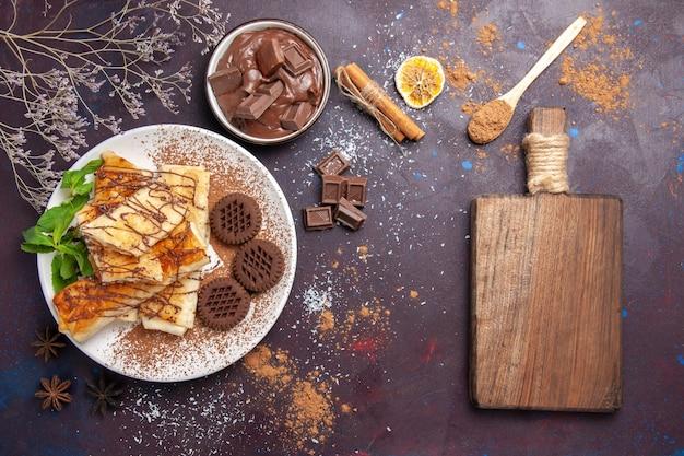 Vue de dessus de délicieuses pâtisseries sucrées avec des biscuits au chocolat sur l'espace sombre