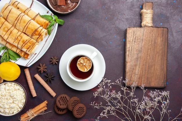 Vue de dessus de délicieuses pâtisseries sucrées avec des biscuits et du thé sur l'espace sombre