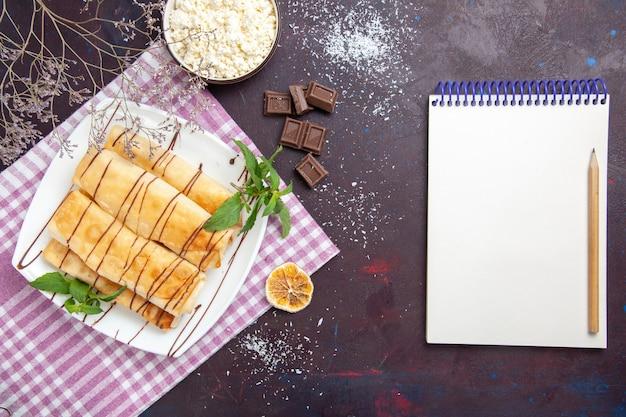 Vue de dessus de délicieuses pâtisseries sucrées avec du chocolat et du fromage cottage sur un espace sombre