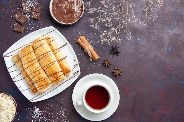 Vue de dessus de délicieuses pâtisseries sucrées avec du chocolat et une tasse de thé sur l'espace sombre